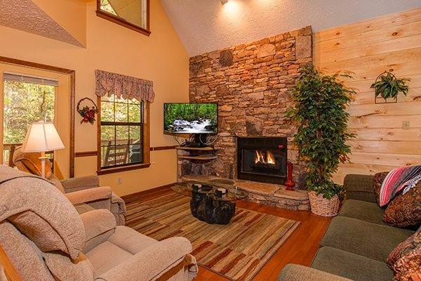 Living room with a fireplace and TV at Lazy Dayz Lodge, a 4 bedroom cabin rental located in Pigeon Forge