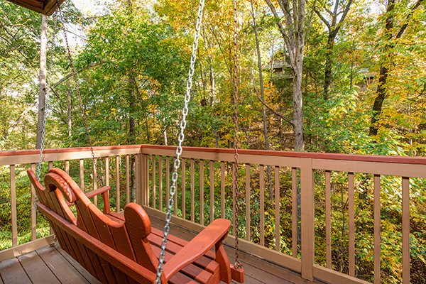 Porch swing facing the woods at Lazy Dayz Lodge, a 4 bedroom cabin rental located in Pigeon Forge