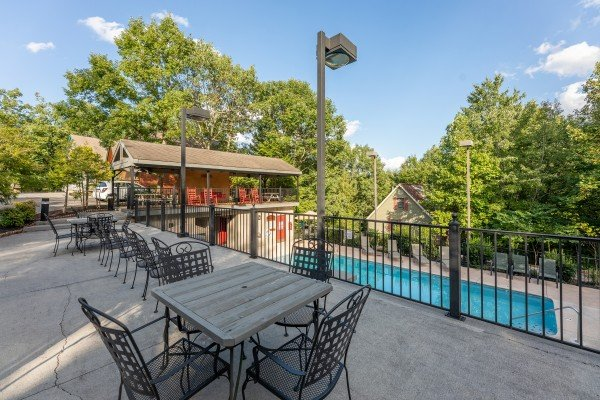 Tables and chairs on the pool deck at Lazy Dayz Lodge, a 4 bedroom cabin rental located in Pigeon Forge