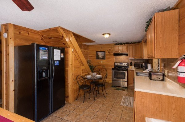 Kitchen with a dining table for three at Pine Splendor, a 5 bedroom cabin rental located in Pigeon Forge