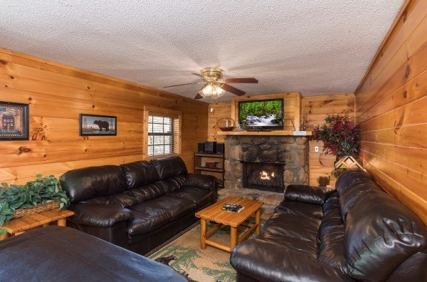 Living room with two sofas, fireplace, and TV at Pine Splendor, a 5 bedroom cabin rental located in Pigeon Forge