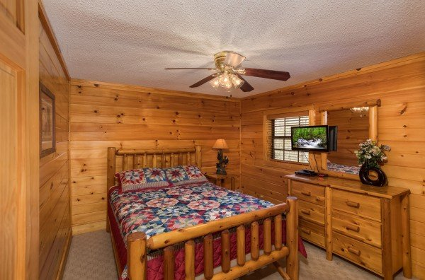 Bedroom with a log bed, dresser, and TV at Pine Splendor, a 5 bedroom cabin rental located in Pigeon Forge