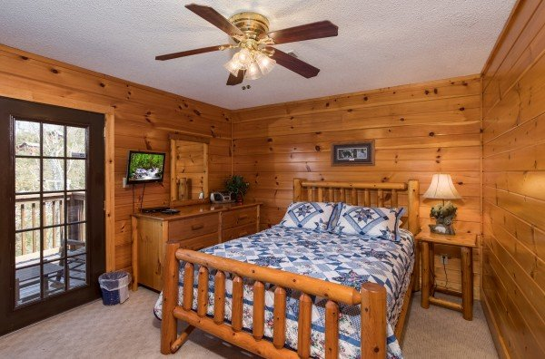 Queen log bed, dresser, and TV in a second floor bedroom at Pine Splendor, a 5 bedroom cabin rental located in Pigeon Forge