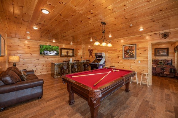 Red felt pool table, arcade game, and bar in the game room at Elk Horn Lodge, a 5 bedroom cabin rental located in Gatlinburg