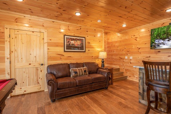Sofa in the game room at Elk Horn Lodge, a 5 bedroom cabin rental located in Gatlinburg