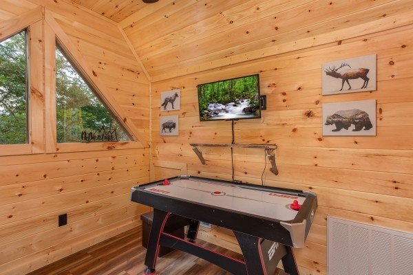 Air hockey table and TV in the loft at Smoky Mountain Treehouse, a 1 bedroom cabin rental located in Gatlinburg
