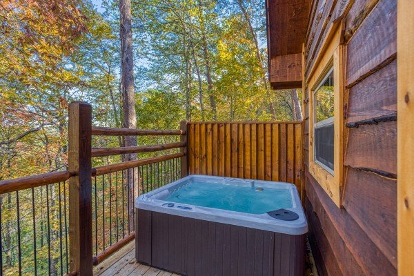 Hot tub on a deck with privacy fence at Smoky Mountain Treehouse, a 1 bedroom cabin rental located in Gatlinburg