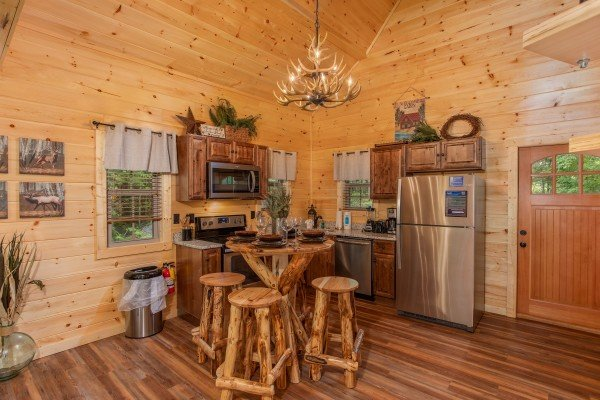 Dining table for four and kitchen at Smoky Mountain Treehouse, a 1 bedroom cabin rental located in Gatlinburg