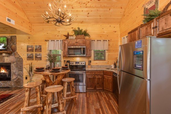 Kitchen with stainless appliances and dining space for four at Smoky Mountain Treehouse, a 1 bedroom cabin rental located in Gatlinburg
