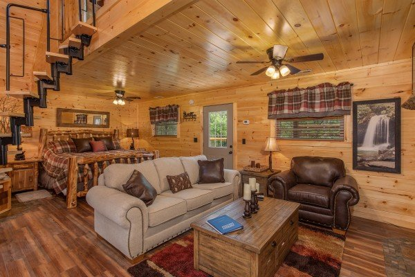 Sofa and chair in the living space at Smoky Mountain Treehouse, a 1 bedroom cabin rental located in Gatlinburg