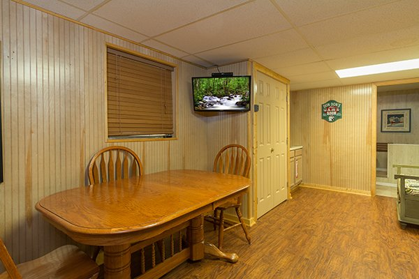 Table and TV in the game room at Up the Creek, a 4 bedroom cabin rental located in Gatlinburg