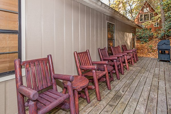 Deck with a grill and log chairs at Up the Creek, a 4 bedroom cabin rental located in Gatlinburg
