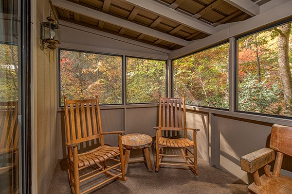 Rocking chairs on a screened porch at Up the Creek, a 4 bedroom cabin rental located in Gatlinburg