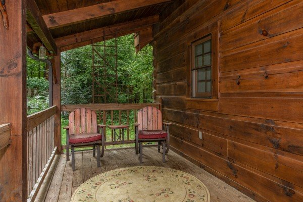 Deck chairs on a covered porch at Stream On! A 2 bedroom cabin rental located in Pigeon Forge