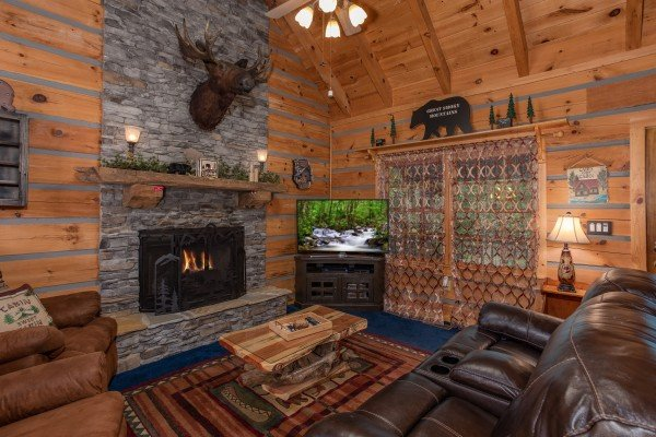 Living room with fireplace and TV at Stream On! A 2 bedroom cabin rental located in Pigeon Forge