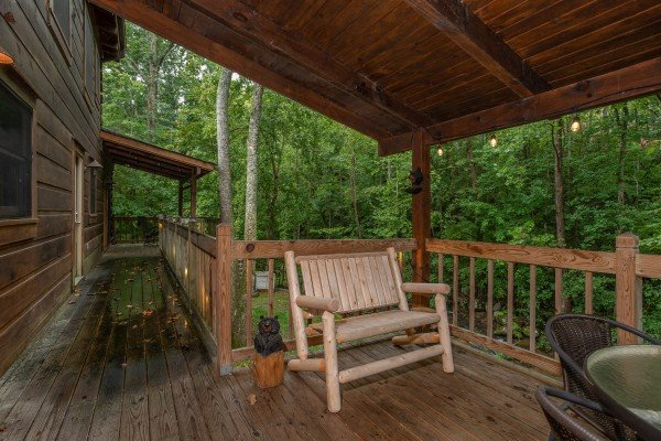 Log bench on a covered porch at Stream On! A 2 bedroom cabin rental located in Pigeon Forge