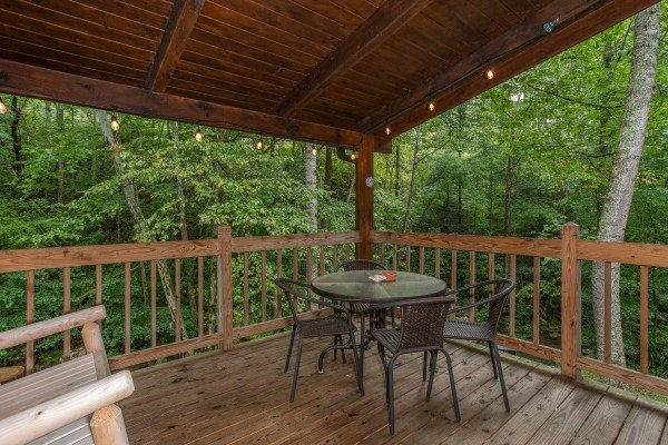 Dining table for four on a covered deck at Stream On! A 2 bedroom cabin rental located in Pigeon Forge