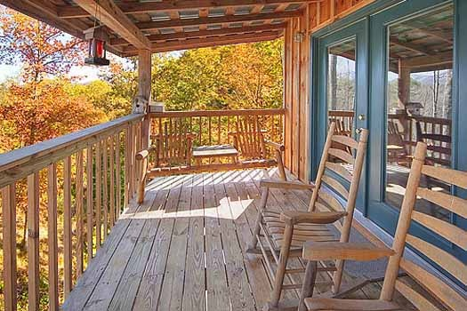 chairs on a covered deck at a finders keepers a 3 bedroom cabin rental located in pigeon forge