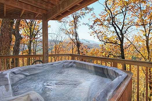 hot tub on covered deck at a finders keepers a 3 bedroom cabin rental located in pigeon forge