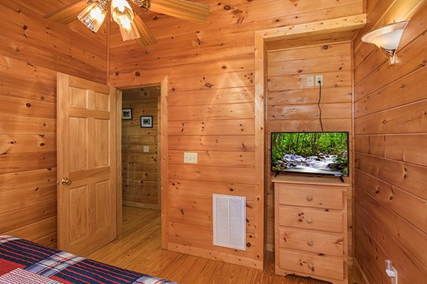 Bedroom with a dresser and TV at Friends in High Places, a 4-bedroom cabin rental located in Pigeon Forge