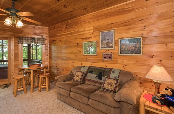 Couch and table with seating for four in the game room at Friends in High Places, a 4-bedroom cabin rental located in Pigeon Forge