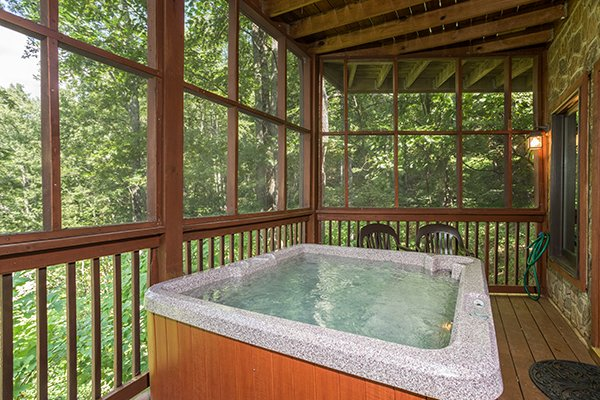 Hot tub on a covered, screened-in porch at Friends in High Places, a 4-bedroom cabin rental located in Pigeon Forge