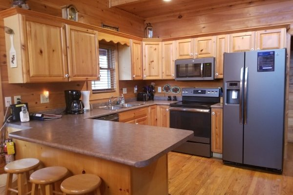 Kitchen with breakfast bar and stainless appliances at Friends in High Places, a Pigeon Forge cabin rental