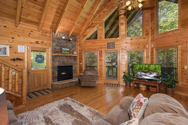 Living room with vaulted ceilings, floor-to-ceiling windows, fireplace, and large TV at Friends in High Places, a 4-bedroom cabin rental located in Pigeon Forge