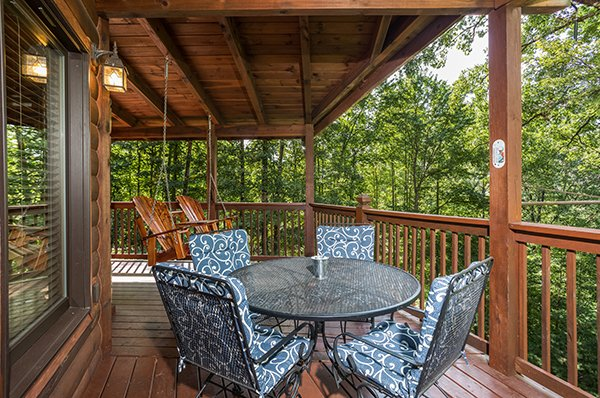 Outdoor dining for four on a covered deck at Friends in High Places, a 4-bedroom cabin rental located in Pigeon Forge