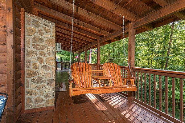 Porch swing on a covered deck at Friends in High Places, a 4-bedroom cabin rental located in Pigeon Forge