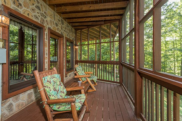 Rocking chairs on a screened-in deck at Friends in High Places, a 4-bedroom cabin rental located in Pigeon Forge