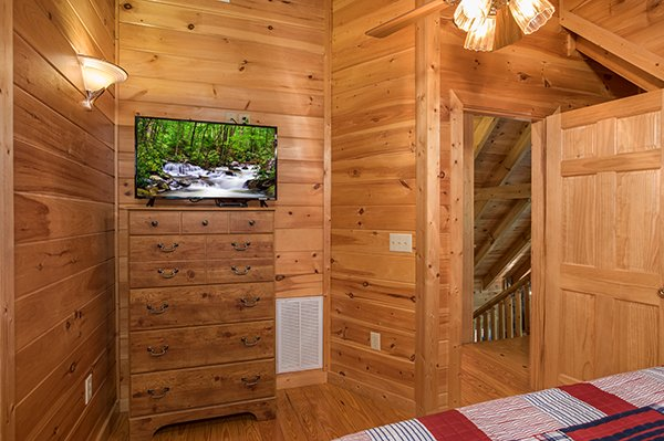 Bedroom with a dresser and fireplace at Friends in High Places, a 4-bedroom cabin rental located in Pigeon Forge
