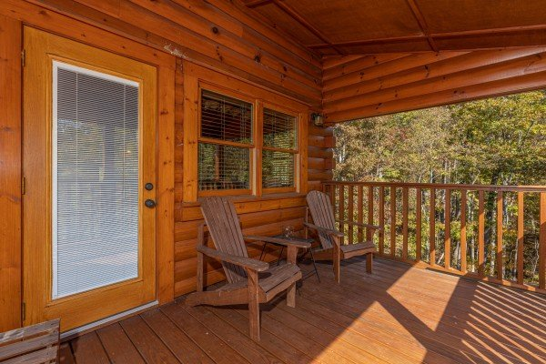 Adirondack chairs on a covered deck at Sensational Views, a 3 bedroom cabin rental located in Gatlinburg