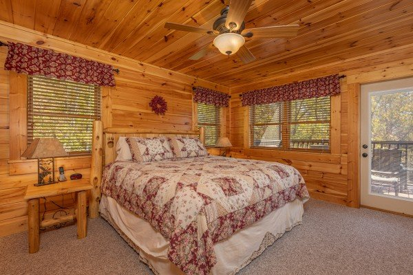 Bedroom with a log bed, two night stands, lamps, and deck access at Sensational Views, a 3 bedroom cabin rental located in Gatlinburg