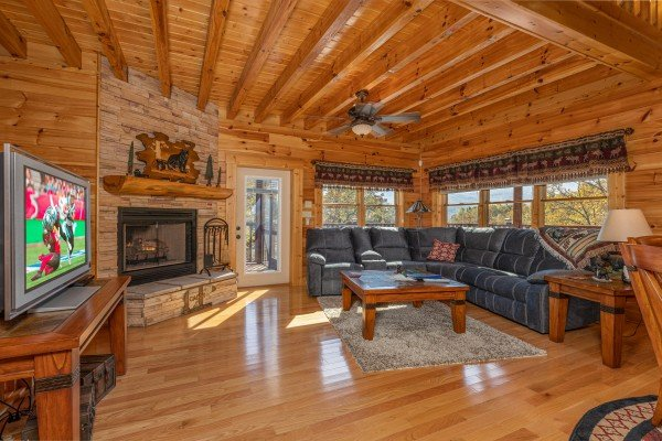 Living room with fireplace, TV, and sectional sofa at Sensational Views, a 3 bedroom cabin rental located in Gatlinburg