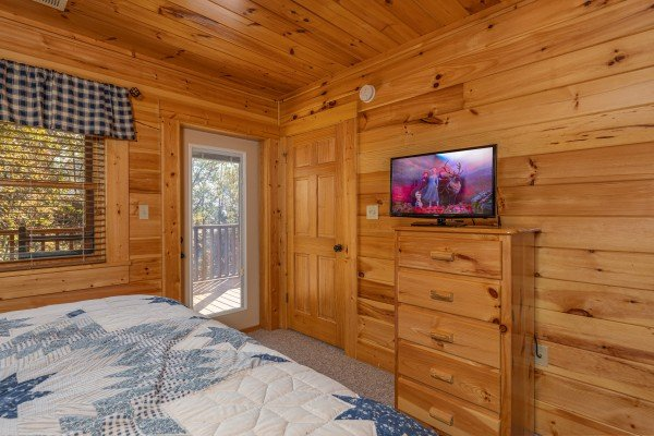 Dresser, TV, and deck access in a bedroom at Sensational Views, a 3 bedroom cabin rental located in Gatlinburg