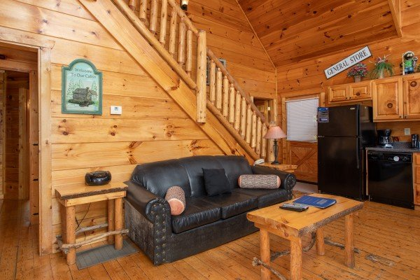 Living room sofa and kitchen with black appliances at Smoky Mountain Mist, a 3 bedroom cabin rental located in Gatlinburg