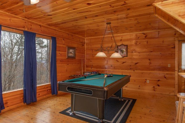 Pool table on the first floor at Smoky Mountain Mist, a 3 bedroom cabin rental located in Gatlinburg
