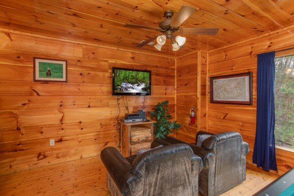 Theater seating and TV on the first floor at Smoky Mountain Mist, a 3 bedroom cabin rental located in Gatlinburg
