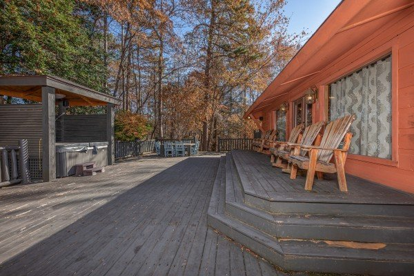 Deck with adirondack chairs, dining table, and hot tub at La Dolce Vita, a 4 bedroom cabin rental located in Gatlinburg