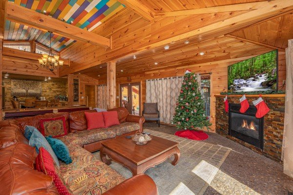 Large sectional sofa with fireplace and TV in a living room at La Dolce Vita, a 4 bedroom cabin rental located in Gatlinburg