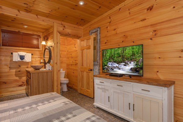 Bedroom with a dresser, TV, and en suite bath at La Dolce Vita, a 4 bedroom cabin rental located in Gatlinburg