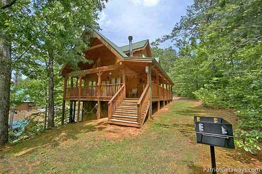 Step down from the deck to the charcoal grill and fire pit at Fox Ridge, a 3-bedroom cabin rental located in Pigeon Forge