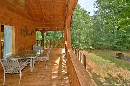 Covered deck with patio dining table and chairs at Fox Ridge, a 3-bedroom cabin rental located in Pigeon Forge