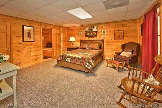 queen bed with attached bath in first floor bedroom at fox ridge a 3 bedroom cabin rental located in pigeon forge