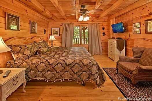 Bedroom with king bed and attached bathroom on the main level at Fox Ridge, a 3-bedroom cabin rental located in Pigeon Forge