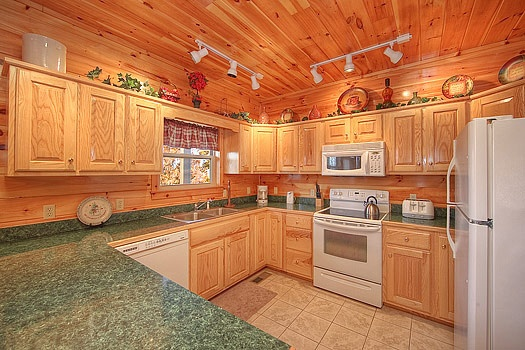 kitchen with white appliances at hickernut lodge a 5 bedroom cabin rental located in pigeon forge