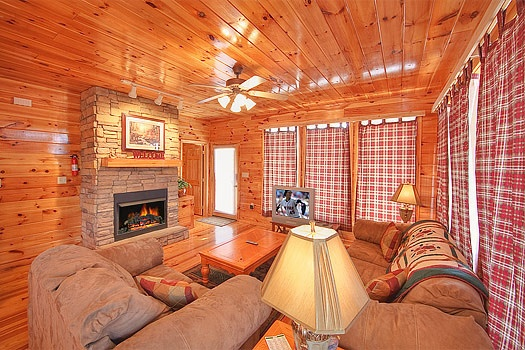 living room with stone fireplace at hickernut lodge a 5 bedroom cabin rental located in pigeon forge