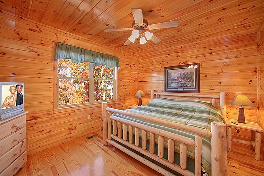 king sized bed in a main level bedroom at hickernut lodge a 5 bedroom cabin rental located in pigeon forge