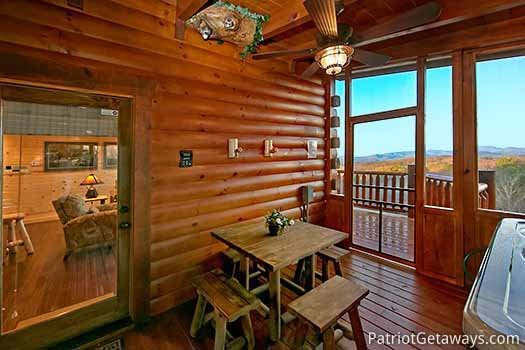 Screened deck with table and chairs by hot tub at Gone to Therapy, a 2-bedroom cabin rental located in Gatlinburg